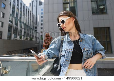 model looking female playing with her smartphone outdoors