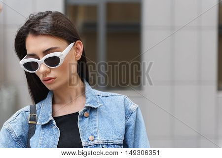 young female designer in glasses in the street with copy space