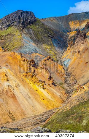 Travel to Iceland in the July. Summer volcanic tundra. WMulti-colored mountains from rhyolite are lit with sun