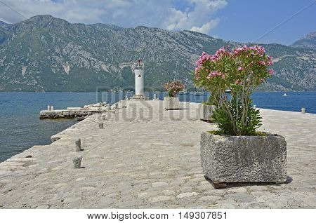 The artificially created island Our Lady of the Rock island in Kotor Bay Montenegro. A small oleander plant can be seen in the foreground and a small lighthouse in the background