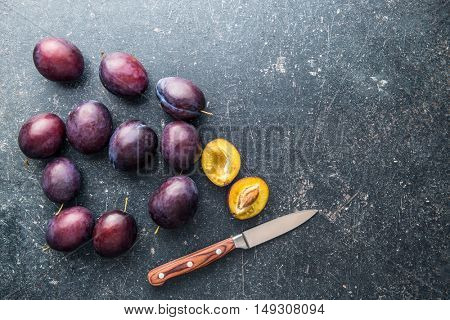 Halved ripe plums and knife on old kitchen table. Top view.