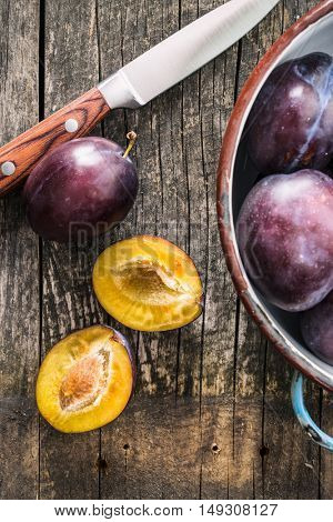 Halved ripe plums and knife on old wooden table. Top view.