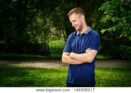 Smiling young man standing relaxed on a green lawn at a summer park.