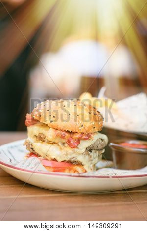 Double cheeseburger on table  in outdoor restaurant with shallow depth of field