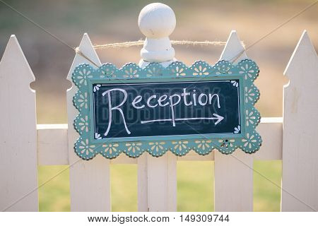 Wedding Reception Sign hanging on a fence.