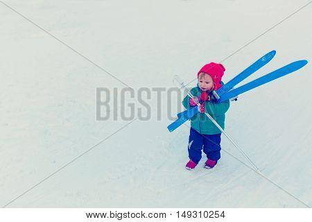 little girl bringing ski in winter snow, kids winter sport