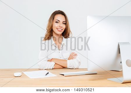 Smiling young businesswoman sitting at the office desk with laptop with hands folded