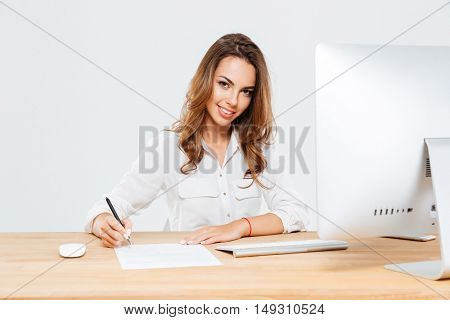 Young smiling businesswoman signing documents while sitting at the office desk