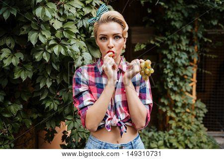 Amazed cute pin-up girl eating fresh white grape outdoors