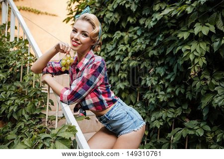 Happy attractive pin up girl with bunch of grape standing and smiling