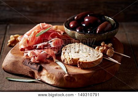 Prosciutto and chorizo with kalamata olives on a wooden board
