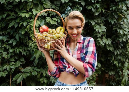 Portrait of cheerful attractive pinup girl with basket of fresh fruits