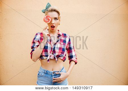 Surprised cute pinup girl covered her eye by lollipop over pink background