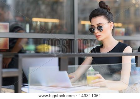 cool woman in glasses working on a terrace of a cafe
