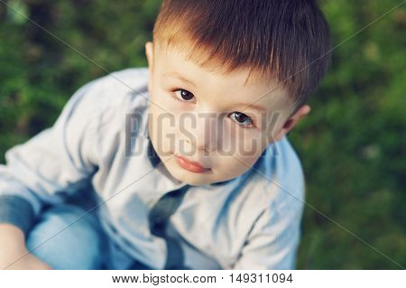 little boy sitting on the grass in park outdoors.