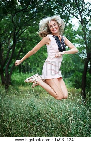 Beautiful happy young woman jumping high in air in the park.