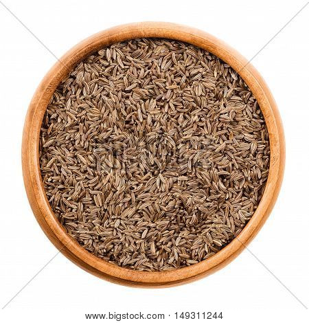 Caraway seeds in wooden bowl on white background. Dried whole fruits of Persian cumin, Carum carvi, with anise like flavor and aroma used as spice in cuisine. Isolated macro photo close up from above.