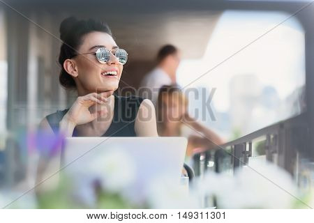 selective focus of a woman smiling on the terrace