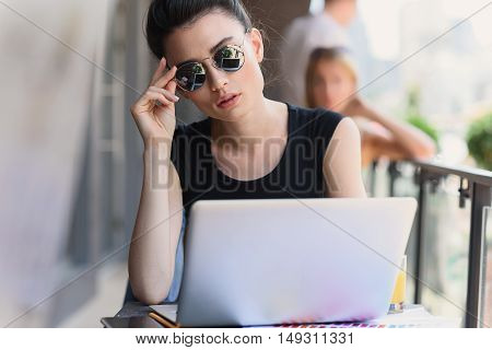 businesswoman in sunglasses sitting in front of laptop