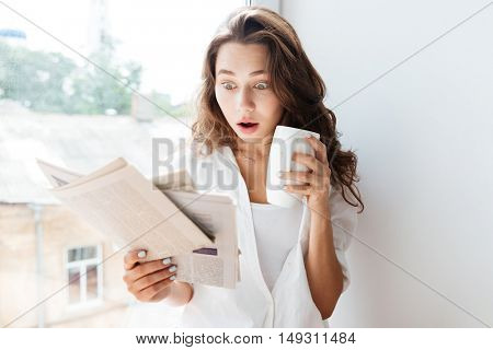 Surprised young brunette woman looking at newspaper and holding tea cup while sitting on the windowsill