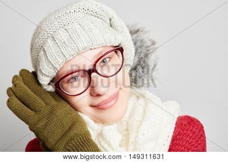 Beautiful young woman wearing a scarf and a cap in winter