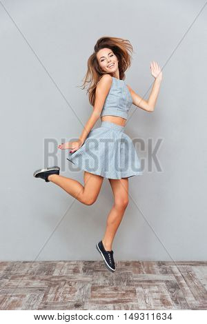 Cheerful playful young woman jumping and running over grey background
