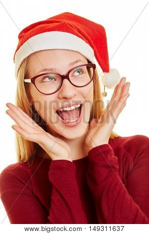Surprised young woman at christmas with her hands on her face