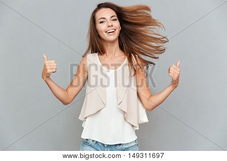 Portrait of a casual smiling young woman showing thumbs up isolated on the gray background