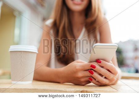 Cropped image of charming young woman with long hair using smartphone in cafe
