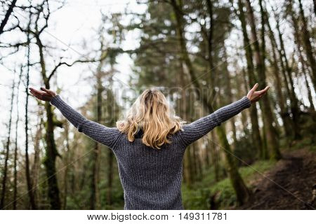 Rear view of woman standing with arms outstretched in forest