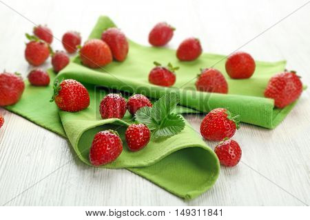 Fresh strawberries on green napkin and white wooden background