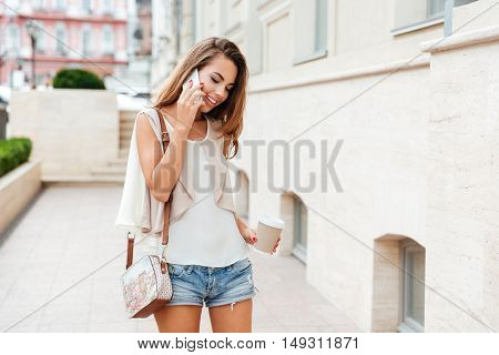 Happy beautiful girl talking on the mobile phone and drinking coffee while walking on the street