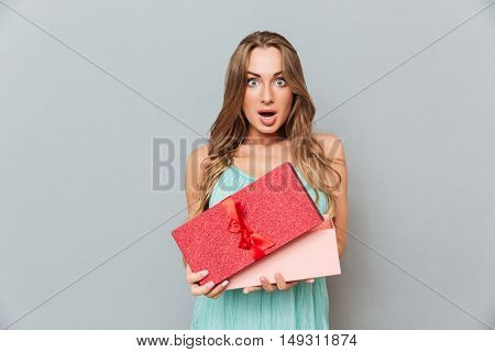 Amazed pretty young woman opening gift box