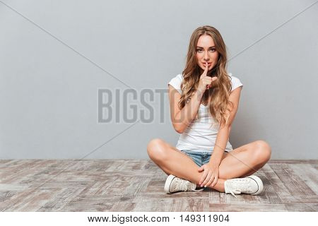 Smiling attractive young woman showing silence gesture while sitting on the floor over gray background