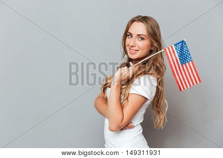 Happy beautiful young woman standing and holding flag of United States of America