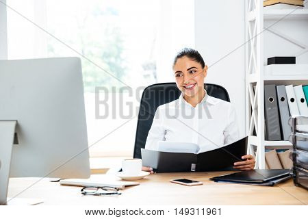 Happy charming businesswoman holding documents and looking at computer screen while sitting at the office desk