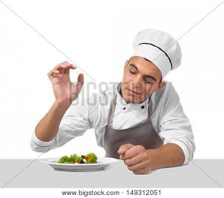 Young handsome chef cook making salad isolated on white