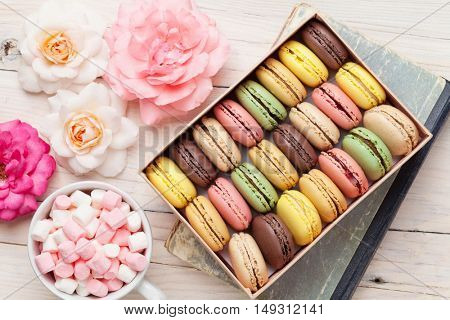 Colorful macaroons and marshmallow on wooden table. Sweet macarons in gift box. Top view