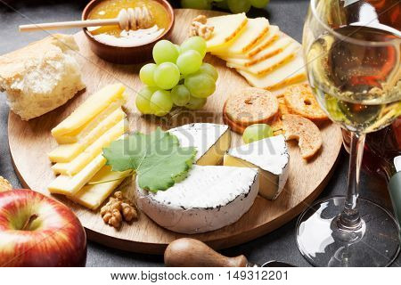 White wine, grape, bread, cheese plate and honey on stone table