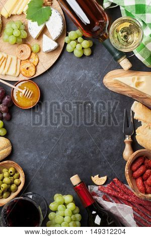 Red and white wine, grape, cheese and sausages over stone table. Top view with copy space