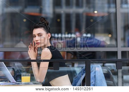 relaxed woman looking into a camera while resting on a terrace of a cafe