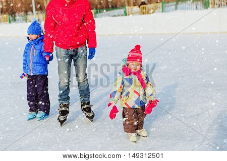 father with two kids skating in winter, family winter sport