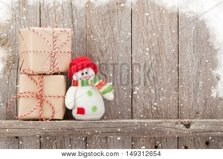 Christmas gift boxes and snowman toy in front of wooden wall with copy space
