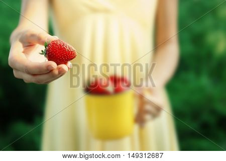 Female hands holding yellow mug with juicy strawberries