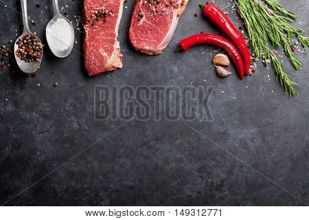 Raw striploin steak with rosemary, salt and pepper cooking over stone table. Top view with copy space