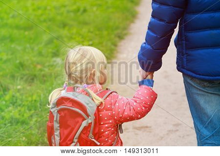 father walking little daughter to school or daycare, kids learning