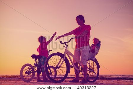 silhouette of father with two kids on bikes, active family