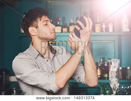 Young handsome barman in bar interior shaking and mixing alcohol cocktail. Professional bartender at work with shaker in hands. Party and nightlife in public places, nightclub occupation