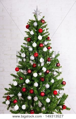 Decorated Christmas Tree With Colorful Balls Over White Brick Wall