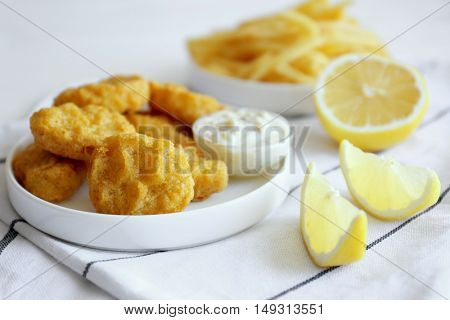 Tasty nuggets with sauce in plate and lemon on napkin